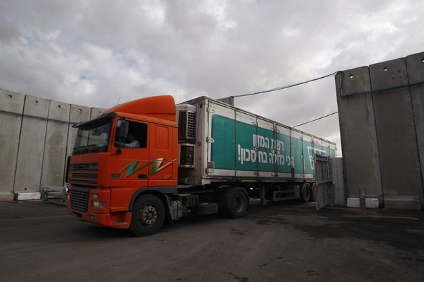 A truck carrying humanitarian goods drives into Kerem Shalom crossing before the transfer of the goods into the southern Gaza
