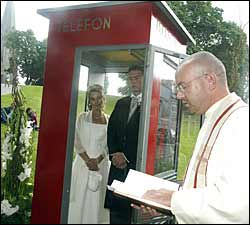 The priest holding a wedding service outside a phone booth to get media attention