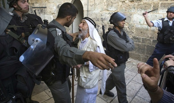 Israeli border police tries to help an Arab Palestinian outside the Temple Mount.