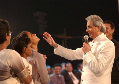 Benny Hinn on stage in India. He wanted money in return for his expences, and got a handsome amount.