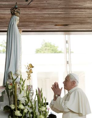 The Pope standing and praying in front of a statue in Portugal.