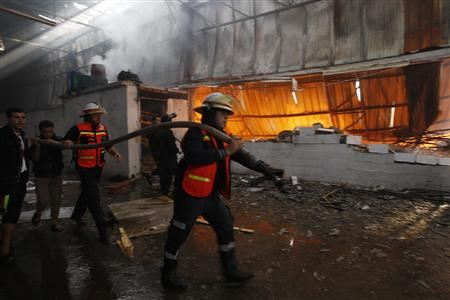 Firefighters try to extinguish a fire at a factory, which according to Palestinians allegedly was hit by an Israeli air strike in Gaza.