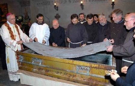 Μια Βατικανό εγκεκριμένο Επίσκοπος βοηθά τους άνδρες κληρικοί και μοναχοί να ανοίξει το φέρετρο του Padre Pio.