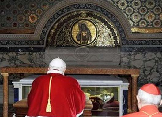 The present Pope stand and pray in front of the corpse of Pius IX. The skull has a face mask.
