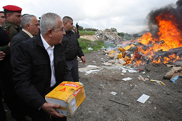 Salam Fayyad, throws a package into a fire set to burn products from Jewish settlements, in the West Bank town of Salfit, Jan 5, 2010.