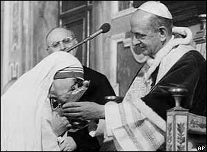 Mother Teresa kissing an idol in the hand of Pope Paul V.