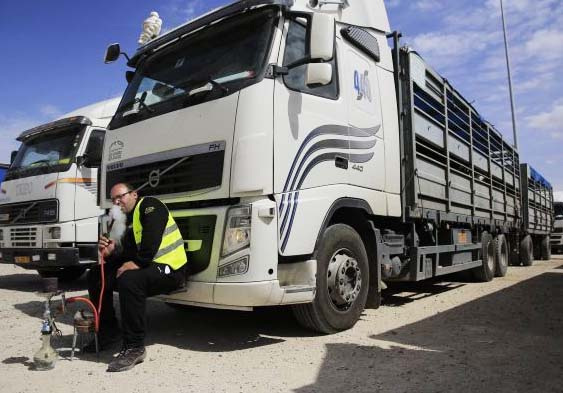 Idling Israeli truck drivers, not permitted by Hamas to drive aid into Gaza.