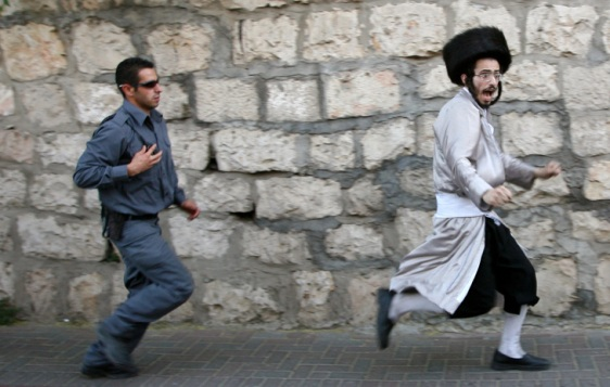An Israeli policeman chase an Ultra Orthodox Jew who have refused to obey orders.