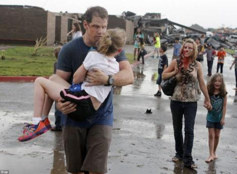 Horror: Teachers carry children away from Briarwood Elementary school after a tornado destroyed the school in south Oklahoma City. The desperate search continued overnight for two dozen children feared dead after yesterday's monstrous tornado, which already took the lives of seven of their classmates.