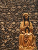 The skull and bones of the claimed saints are behind this idol of the Madonna.