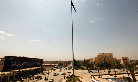 The flag of the Islamist rebel group Jabhat al-Nusra flies over the main square of the city of Raqqa