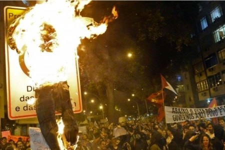 Angry protestors burn an effigy of the Pope, claiming waist of public money as reason.