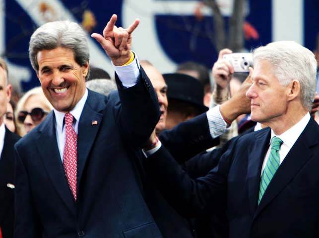 A smiling John Kerry identify and greets an Order brother in the room.
