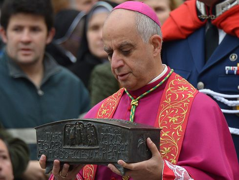 Italian archbishop Rino Fisichella holds the ashes of Saint Peter before a ceremony at the Vatican, on November 24, 2013.
