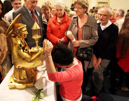 Bowing in religious worship before a statue of gold and a piece of flesh.