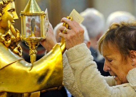 A British woman hold hands with a golden statues, and pray to a piece of rotten human flesh.