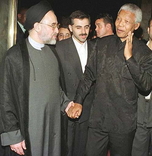 Nelson Mandela hand in hand with former Iranian president Muhammed Kanthami.