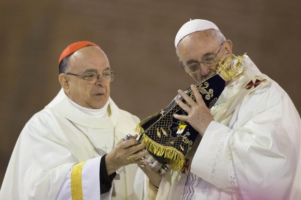 The Pope kisses an idol of stone wood.