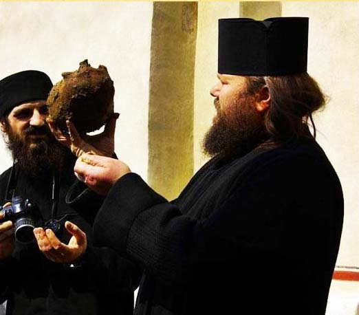 A priest at Lainici monastery lift up the cut off skull of the abbot.