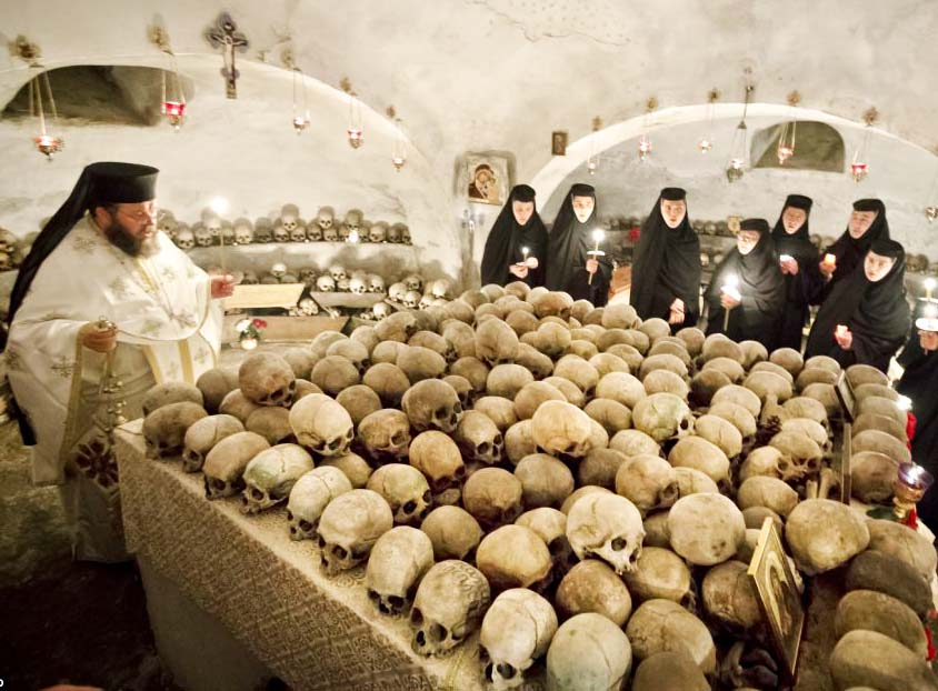 A Orthodox priest perform his religious duties in front of a table with skulls.