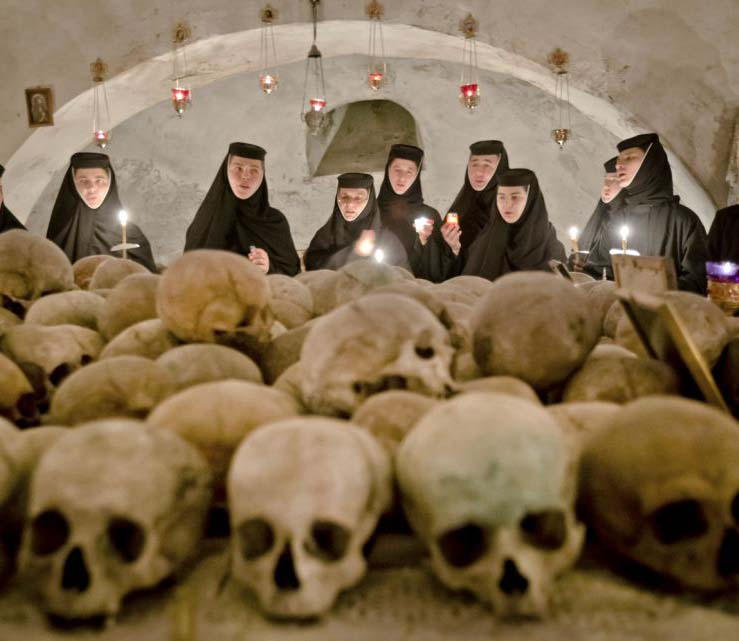 The nuns watch the cut of skulls. They might be the remains of Protestant martyrs.