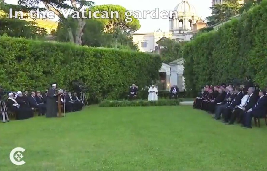 "An Imam is singing prayers to ""allah"" as a start of this garden party."
