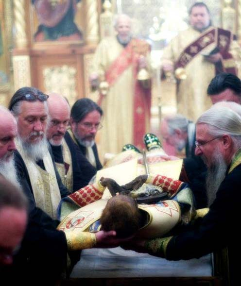 Religious men from Russia place the corpse for display in their chruch, after de redreessing is over.