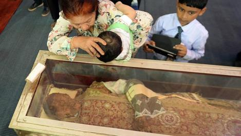 Even small children are forces to kiss the glass box wich contains the 500 year old corpse.