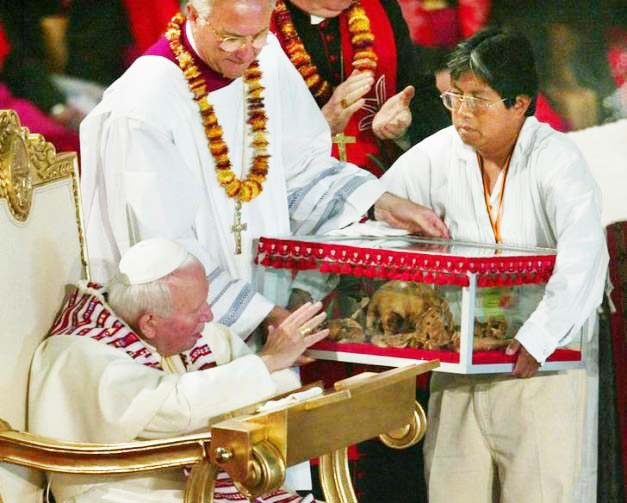 The late Pope reaches out to a Mexican skull, and wants to bless it.