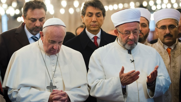 The Pope deeply into prayers towards Mecca, visiting a mosque in Istanbul.