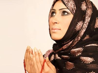 A Muslim woman using a chanting chain when she prays towards Mecca.
