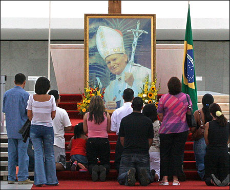 Bewitched Catholics kneel and worship their Pope.