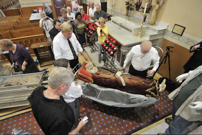 The corpse is transported up the altar of the rleigious shrine.