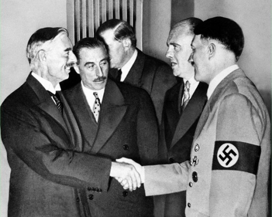 "Neville Chamberlaine makes Hitler a ""peace partner"" in Munich in 1938."