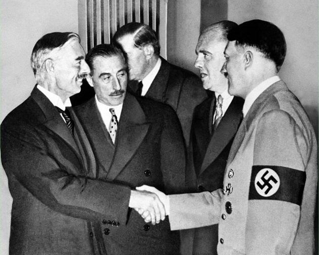 "Neville Chamberlaine makes Hitler a ""peace partner"" in Munich in 1938."