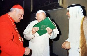 The Pope kisses a Koran in front of a Cardinal and a Muslim leader.