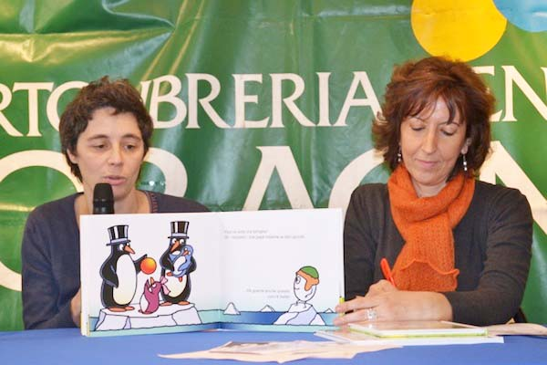 Francesca Pardi (left) present her book, with two guy penguines paranting a child.