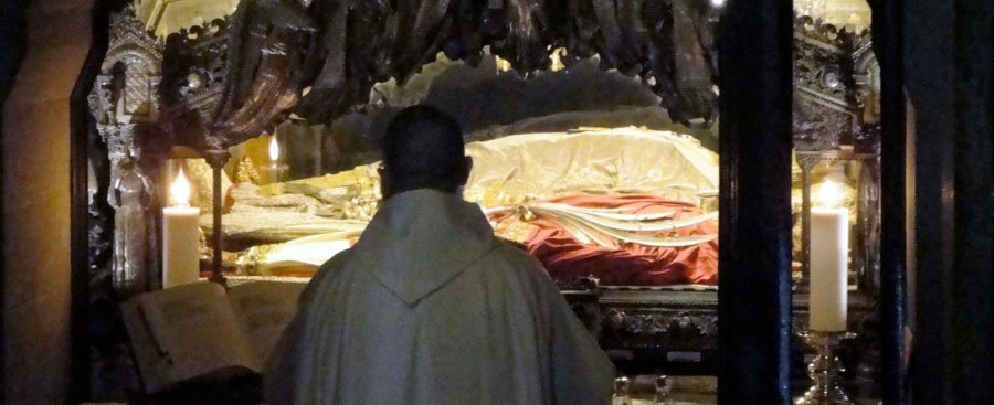 A mass is conducted infont of the corpse of the ancient Bishop of Milan.