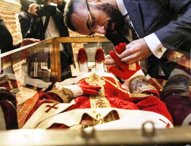 It require a lot of patiance to dress up a dead Pope. From where did they get the idea of putting red shoes?