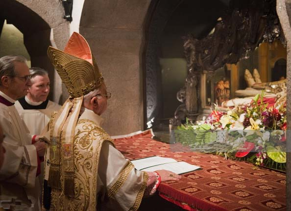 A Catholic Bishop conduct his religious ritials infront of the the corpses.