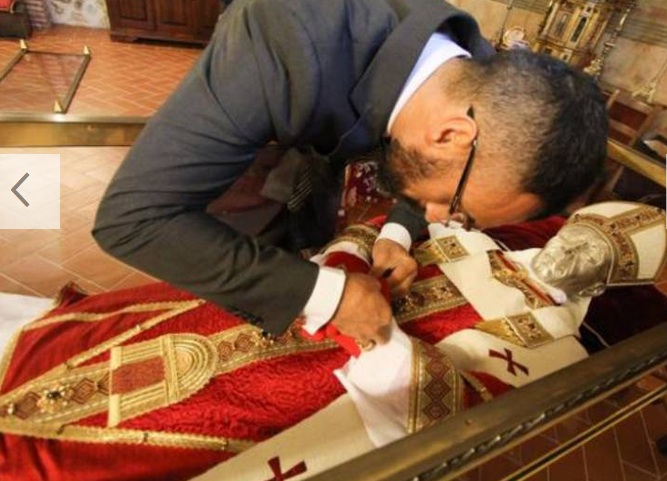 A local Catholic in Central Italy dress up a dead Pope to get him ready to meet Pope Benedict.