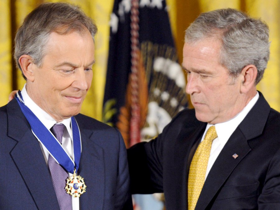 War Criminal George W. Bush gives a medal of honor to his brother in crimes.
