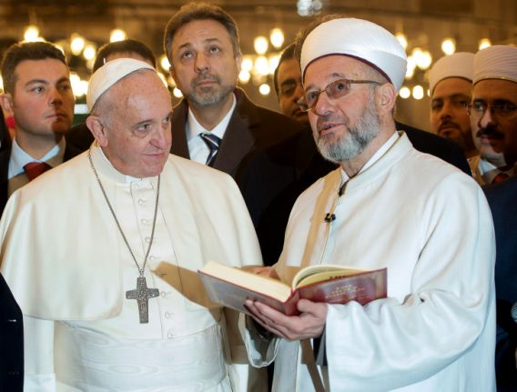 The Grand Mufti of Istanbul, Rahmi Yaran, right, shows Pope Francis the Quran, the Muslim holy book, at the Sultan Ahmet mosque in Istanbul, Turkey, Saturday, Nov. 29, 2014.