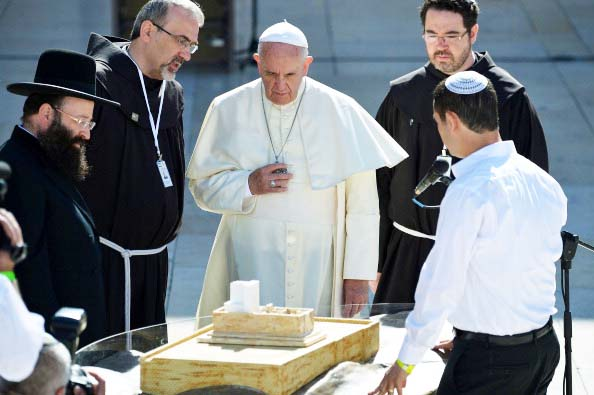 Pope Francis (C) looks at model of the planned Third Temple with religious leaders near the Western Wall, Judaism's holiest site, in Jerusalem's Old City on May 26, 2014. Pope Francis faces a diplomatic high-wire act as he visits sacred Muslim and Jewish sites in Jerusalem on the final day of his Middle East tour AFP PHOTO/ VINCENZO PINTO (Photo credit should read VINCENZO PINTO/AFP/Getty Images)