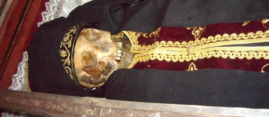"""The skleton and skull of the """"holy saint"""" is dressed up in garments of an Orthodox priest."""