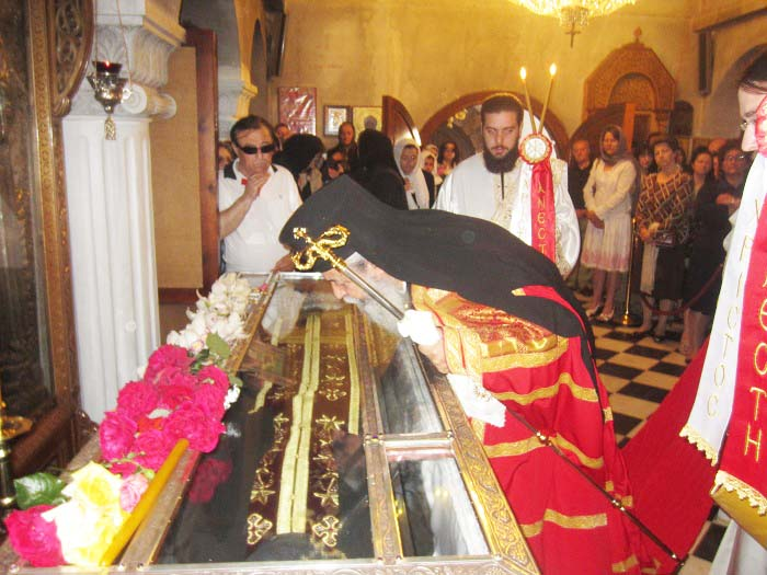 The achbishop kiss the coffin with teh dressed up remains of Ephraim.