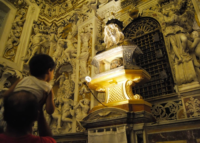 Small children are lifted up to see the skull that is placed above the altar.